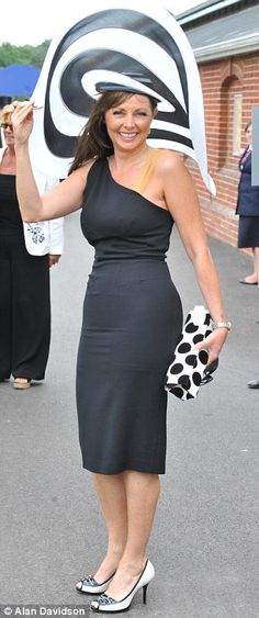TV presenter Carol Vorderman shelters under the brim of her monochrome hat
