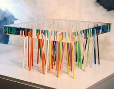 Shibafu table created by Japanese based company Emmanuelle Moureaux Architecture and Design. The designer used 56 slender coloured acrylic sticks, embedded randomly