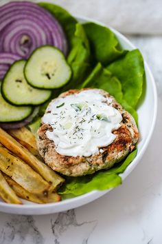 These Greek Chicken Burgers are paleo, whole30, keto, and AIP! They're topped with a dairy-free tzatziki and feature traditional Greek-inspired flavors. #whole30 #keto #aip #paleo #greekburger #chickenburger #healthy