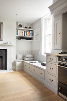 Georgian Farmhouse Kitchen, Hampshire - Humphrey Munson Kitchens - banquette seating next to the Lacanche range cooker with storage drawers underneath.