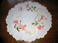 A very nice silk embroidery round measuring 20 inches across in a rose pattern. Check out this awesome WorthPoint article!