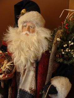 Woodland Treasures  by The Santamaker - This Father Christmas imparts a rustic feeling of warmth and generosity. Dressed in wools , he is a friend to the many animals he encounters on his journeys. He wears a coat of navy wool with a center inset of an antique quilt and holds a basket with a fawn curled up along the pinecones and berries.