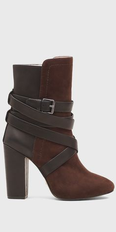 Live on the edge in these statement-making leather and suede combo booties, sitting atop a chunky high heel. Bold wraparound straps buckle to close. Height: 4