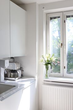 Homevialaura   White kitchen with marble countertop and white lilies