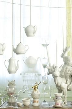 These are lights!  Hanging teapots either lights or props would be an amazing decoration at a Mad Tea Party!