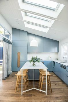 kyal and kara renovation blue kitchen with light wooden floorboards and skylights