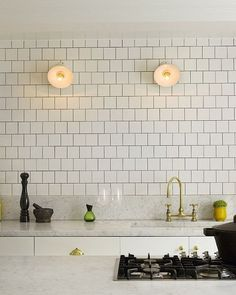 Subway tile with dark grout, marble counters and brass accents...