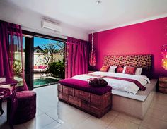 girls room with hot pink wall and curtains. extra storage at the end of bed