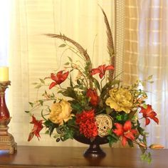 "Elegant Red Lilly Centerpiece with Feathers AR322. Beautifully designed centerpiece in metal bowl adds a lovely accent to your homes décor. Created wth deep red tiger lilles, hydrangeas, peonies and feathers with grasses. 24""L x 16"" W"
