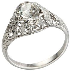 Edwardian 1.31 Carat Diamond Engagement Ring. This is a beautiful and feminine Edwardian engagement ring which features a 1.31ct J-SI1 diamond (EGL) accented by nine small round diamond side stones with lovely filigree, open-work, and engraving. Circa 1915.