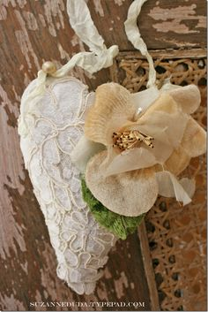 I used a vintage linen napkin to make my hearts. I sewed it and stuffed it, then hand sewed on some vintage lace from a wedding dress. I added a velvet flower from an old hat, and some pearl buttons to attach the ribbon.