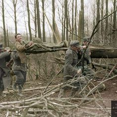 the_ww2_memoirs An American soldier belonging to the 104th Infantry Division smiles at the camera while four German POWs under armed escort carry him to an aid station behind the front lines during the opening days of Operation Grenade, near the Roer River, Germany, 23rd of February, 1945. This soldier was injured by German mortar fire shortly after crossing crossing the Roer River. He had serious shrapnel wounds on his left arm and took one hit to the helmet but luckily it did not…
