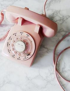 Maggie has a pale pink dial up phone on her bedside table.