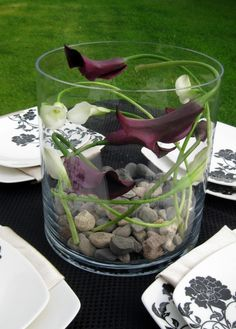 Calla lillies in short vase swirled on table.
