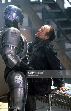 Peter Weller grabs Kurtwood Smith by the neck in a scene from the film 'RoboCop', Kurtwood Smith, Robocop 2, Peter Weller, Paul Verhoeven, Tv Show Games, Sci Fi Films, Bd Comics, Science Fiction, Fiction Movies