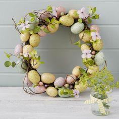 Deko Idee mit einem Kranz aus pastelligen Eiern und Zweigen