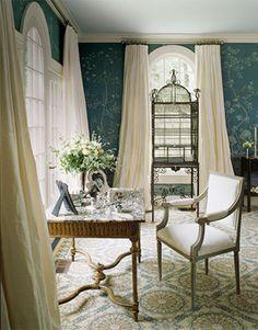 A Louis XVI writing desk tucked amongst creamy silk taffeta curtains and avian-themed de Gournay wall panels.