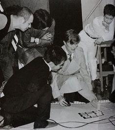 Bowie with Sukita, checking test Polaroids, 1980