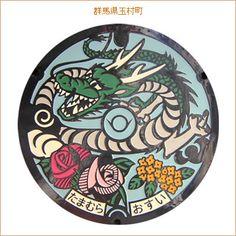 玉村町の地名伝説に登場する「竜」と「玉」を上部に、下部には町の花木「バラ」と「もくせい」、中心には町章を入れたデザインになっている。