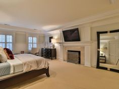 With its own fireplace, a flat-screen TV and plenty of space, the home's master bedroom feels grand and luxurious. Light walls and beige carpet pair with dark furniture, creating contrast and interest within the space.