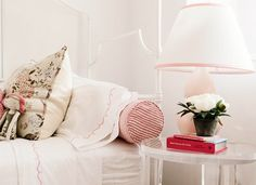 Pink and pretty bedroom with small flowers on bedside table