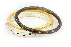Three Fabulous Bangle Bracelets. The black one is sterling silver with oxidation and diamonds. Silver one is Sterling with black diamonds. The yellow one is Sterling with gold plate and diamonds.