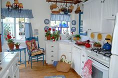 Vintage Kitchen Design Idea in White Theme with White Cabinets and White Ceramic Countertops and Wood Ceiling Pot Rack also Blue Accent from Window Curtains and Valances and Blue Classic Chair and Table