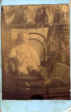 Probable post mortem photograph of a little boy. There is something not quite right about his eyes and positioning in the chair.
