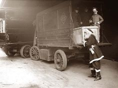 Santa Claus loading a railway express car with toys, 1920
