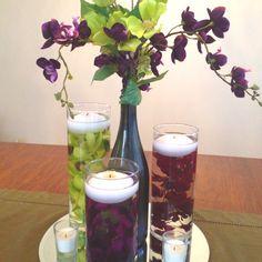 Possible centerpiece. Floating candles + wine bottle vase.
