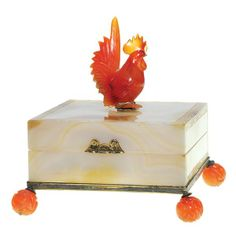 Edward Farmer Chinese agate box lofted on four ball feet and adorned with a cockerel strutting on top. Carved from the reddish brown mineral carnelian, silver mounts and the top and sides have a simple design rngraved on the edges