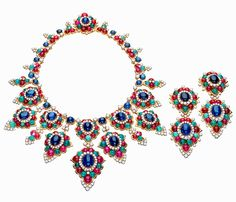 A necklace with matching pendent earrings from 1967 in yellow gold, with cabochon emeralds, rubies and sapphires highlighted with brilliant-cut diamonds.