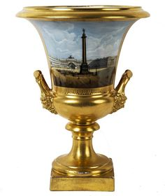 A RUSSIAN IMPERIAL PORCELAIN VASE WITH IMAGE OF ALEXANDER COLUMN, RUSSIAN IMPERIAL PORCELAIN FACTORY, 1840-1855, the urn-shaped vase with a hand-painted detailed view of the Alexander Column flanked by two gilded handles in joined to the body by two bearded masks at each base, the rim and base fully gilded, height: 26.4 cm (10 3/5 in.), blue underglazed imperial cypher of Nicholas I on base