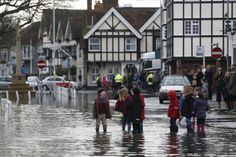 Children greet one another in a flooded street the village of Datchet on 10 February after the nearby River Thames burst its banks during the wettest ever January on record, Berkshire, England, United Kingdom, 2014, photograph by Sang Tan.