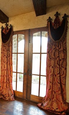 long pooling panels with swag valances that are hung with 3 tie backs