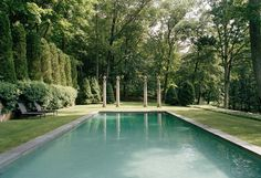 At the end of the pool, American columns topped with French urns create a boundary between the pool area and the forest.