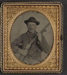 [Unidentified soldier in Confederate uniform with Berdan's Sharps rifle and Colt 1862 Police Model pistol]