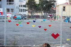 """via craftzine:  """"Residents of Wellington City, New Zeland joined forces with the folks behind OutdoorKnit and beautified this fence on a corner in their community where development has come to somewhat of a standstill. A group gathered on a Sunday afternoon to weave colorful hearts into the spaces on the chain link fence. The effect from a distance looks as though all the hearts are simply floating in air. I love this kind of craftivism, and seeing folks of all ages participate makes it even…"""