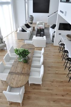Modern space - bright white walls and furniture; sleek surfaces, modern art, PLUS a beautiful, rustic harvest dining table
