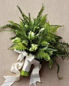 This lush clutch of ferns (here with parrot tulips) is a winner for two reasons: It's inexpensive, and it works for weddings year-round. Bound with two creamy ribbons, the rich textures and colors provide a refreshing alternative to hothouse blooms.