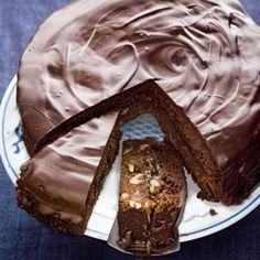 Chocoladetaart Ingrediënten: 225 g boter   extra om in te vetten  3 tabletten chocolade extra puur 72% (a 100 g), in kleine stukjes  200 g rietsuiker  5 eetlepels vloeibare honing  4 eieren, gesplitst  200 g bloem  1 theelepel bakpoeder (pakje 80 g)  1 eetlepel cacaopoeder  2 zakjes walnoten (a 50 g), gehakt  150 g gedroogde abrikozen zonder pit (zak 375 g), in reepjes  300 g abrikozenjam  2 eetlepels zonnebloemolie Allerhande 12, 2009