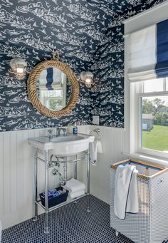 The sea-faring theme continues in the bunkroom bath, with nautical-themed wallpaper and accessories by Serena & Lily, console sink and faucet by American Standard and blue penny round tile by Tile America.