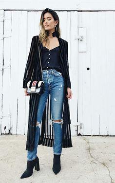Choker de argola, blusa preta com botões, calça jeans rasgada no joelho, ankle boot preta, maxi casaco preto com transparência listrada