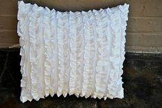 Pillow for reading chair...white slipcovered chair, white ruffled pillow, soft pink blanket