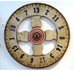"Carnival Game Wheel    Large wooden carnival game wheel, 42"" diameter, very attractive paint decoration, late 19th or early 20th Century, American. Makes a great wall hanging.      Price: $1,950."