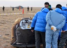 Retrieval team members inspect China's lunar test capsule after its landing on Oct. 31, 2014.