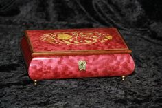 I have a music box like this, although the design on top might be slightly different.  I love the floral inlay with wine red.  My is an 18 note that plays the 'Blue Danube Waltz'.