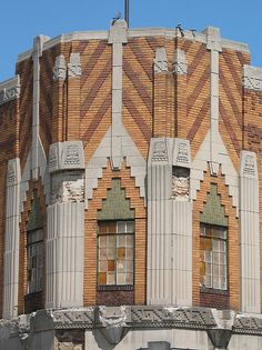 A detail of the corner tower showing the Mayan stepped arch motif and glyph-like details above the fluted pilasters. The chevrons are another standard art deco design element.