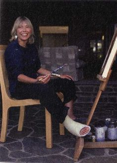 Joni Mitchell, singer, songwriter  painter, at her easel.