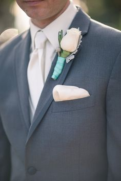 Groom in gray suit, ivory silk tie + pocket square with ivory rose boutonniere wrapped with aqua ribbon {Oz Visuals}